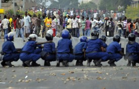 Burundian riot police form a barricade to hold protesters back during a demonstration against the president's bid to cling to power for a third term in Musaga, outskirts of Bujumbura, on April 28, 2015. At least five people have died since clashes broke out on April 26 after the ruling CNDD-FDD party, which has been accused of intimidating opponents, designated President Pierre Nkurunziza its candidate in the June 26 presidential election. AFP PHOTO / SIMON MAINA        (Photo credit should read SIMON MAINA/AFP/Getty Images)