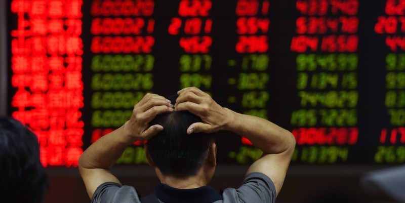 An investor looks at screens showing stock market movements at a securities company in Beijing on July 14, 2015.        (Greg Baker/AFP/Getty Images)
