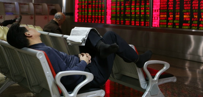 BEIJING, CHINA - JANUARY 08: (CHINA OUT) An investor naps while observing stock market at an exchange hall on January 8, 2016 in Beijing, China. Chinese stock market experienced a halt on Thursday and rebounded the next day. The Shanghai Composite Index rose 2.39% to 3199.56 points and the Shenzhen Composite Index went up 1.98% to 10973.12 points. (Photo by ChinaFotoPress)***_***