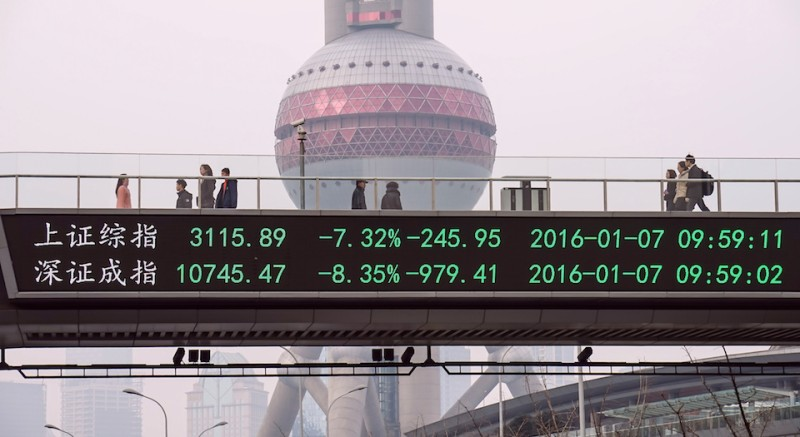 CORRECTION-CITY IN METADATA People walks along a pedestrian bridge with a screen showing stock market movements in Shanghai on January 7, 2016. China's market regulator on January 7 extended restrictions on big shareholders selling stocks, on whom a ban had been due to expire at the end of the week, as trade was suspended in the morning following a seven percent plunge.          AFP PHOTO   CHINA OUT / AFP / STR        (Photo credit should read STR/AFP/Getty Images)