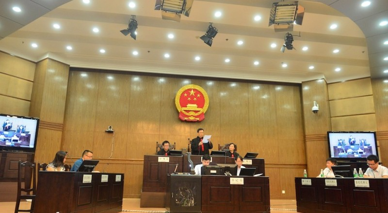 China rape victim's mother Tang Hui (L) sits in the Hunan Provincial People's High Court in Changsha, central China's Hunan province on July 15, 2013.  The court awarded damages to the mother of a rape victim after she was sent to a labour camp for demanding her daughter's attackers be punished, a spokesman said on July 15.   CHINA OUT     AFP PHOTO        (Photo credit should read STR/AFP/Getty Images)