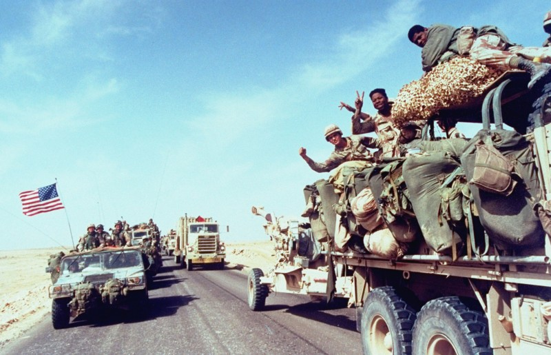 During the first Gult War, named Operation Desert Storm, American soldiers wave to the camera from a truck as their convoy moves into Iraq, February 24, 1991. (Photo by Ken Jarecke/Department Of Defense (DOD)/The LIFE Picture Collection/Getty Images)