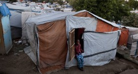 PORT AU PRINCE, HAITI - JANUARY 2011: A young boy sits by his familiy's makeshift home at a tent camp, where 55,000 displaced Haitians are living on the grounds of what was the Club de Petionville January, 2011 in Port au Prince, Haiti.  (Photo by Jonathan Torgovnik/Getty Images)