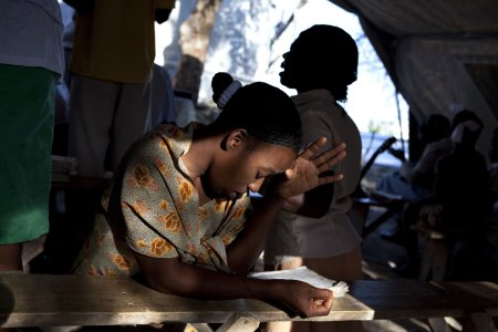 PORT AU PRINCE, HAITI - JANUARY 2011: A woman prays at a makeshift church at a tent camp, where 55,000 displaced Haitians are living on the grounds of what was the Club de Petionville January, 2011 in Port au Prince, Haiti. (Photo by Jonathan Torgovnik/Getty Images)