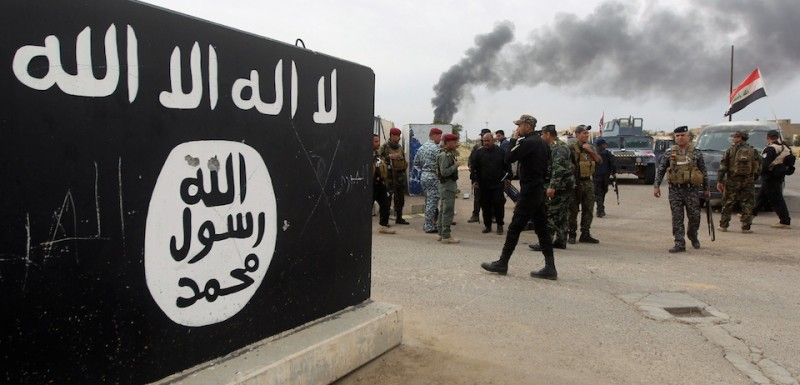 Iraqi security forces and Shiite fighters from the Popular Mobilisation units gather next to a mural depicting the emblem of the Islamic State (IS) group outside one of the presidential palaces in Tikrit, on April 1, 2015, a day after the prime minister declared victory in the weeks-long battle to retake the city from the IS group. Iraqi forces battled the last jihadists the northern city on April 1, 2015 to seal a victory the government described as a milestone in efforts to rid the country of the Islamic State group. AFP PHOTO / AHMAD AL-RUBAYE        (Photo credit should read AHMAD AL-RUBAYE/AFP/Getty Images)