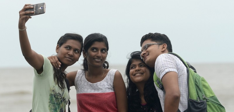 In this photograph taken on June 15, 2015, young Indian students take a 'selfie' on Marine Drive promenade in Mumbai. Selfies have become a global phenomenon with users rarely missing an opportunity to snap a photo of themselves, whether it be in front of a world-famous landmark or simply at dinner with friends. While people may have enjoyed having their photo taken since self-portraits first appeared in 1839, the invention of smartphones with front-facing cameras is fuelling a different type of selfie in the 21st century. A Pew Research Center poll last year estimated that more than half of 18-33 year olds had taken their own portrait before sharing it on social networks online. The phenomenon has fuelled special technology to help users take the perfect shot, most notably the now-ubiquitous selfie stick.   AFP PHOTO/ Indranil MUKHERJEE        (Photo credit should read INDRANIL MUKHERJEE/AFP/Getty Images)