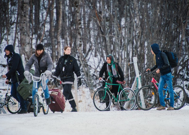 Refugees walk alongside there bikes to the Norwegian border crossing station at Storskog after crossing the border from Russia on November 12, 2015 near Kirkenes. An increasingly popular route for migrants across Russia and into Norway has Oslo angered and worried as winter approaches, while commentators suspect Moscow is deliberately creating problems for its neighbour.       AFP PHOTO / JONATHAN NACKSTRAND        (Photo credit should read JONATHAN NACKSTRAND/AFP/Getty Images)