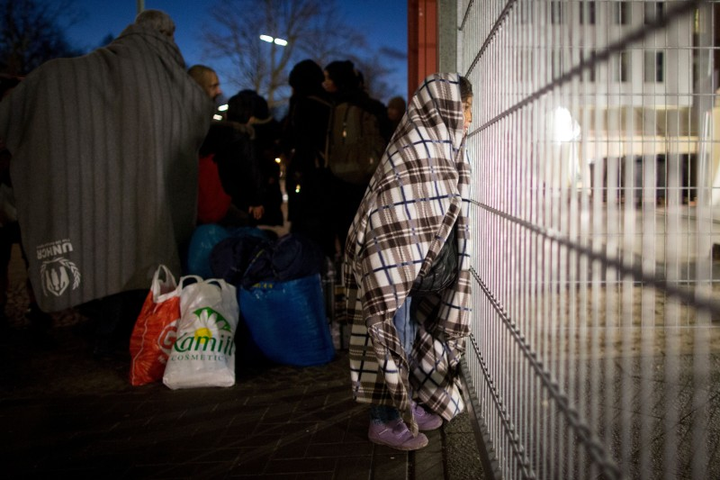 Asylum seekers from Syria stand at the fence of the State Office of Health and Social Affairs (LAGeSo) registration centre in Berlin on December 21, 2015.  / AFP / dpa / Kay Nietfeld / Germany OUT        (Photo credit should read KAY NIETFELD/AFP/Getty Images)