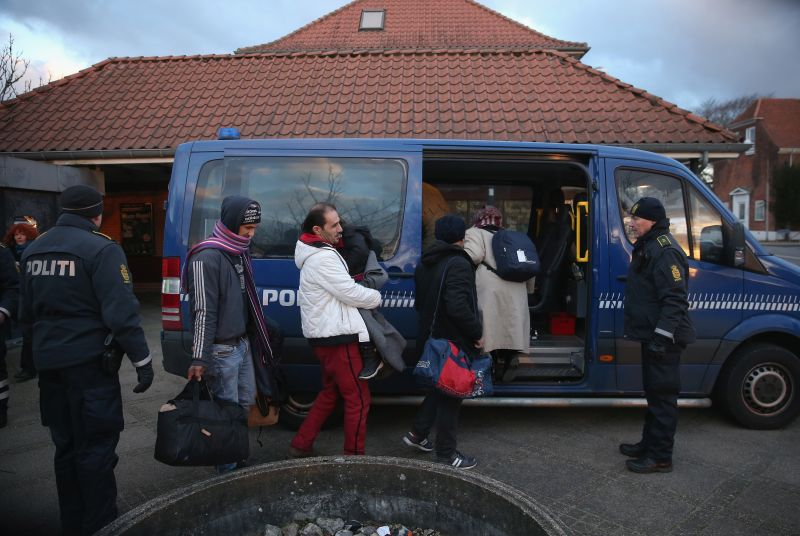 PADBORG, DENMARK - JANUARY 06:  Danish police escort a family from Syria seeking asylum in Denmark after finding them while checking the identity papers of passengers on a train arriving from Germany on January 6, 2016 in Padborg, Denmark. Denmark introduced a 10-day period of passport controls and spot checks on Monday on its border to Germany in an effort to stem the arrival of refugees and migrants seeking to pass through Denmark on their way to Sweden. Denmark reacted to border controls introduced by Sweden the same day and is seeking to avoid a backlog of migrants accumulating in Denmark. Refugees still have the right to apply for asylum in Denmark and those caught without a valid passport or visa who do not apply for asylum are sent back to Germany.  (Photo by Sean Gallup/Getty Images)