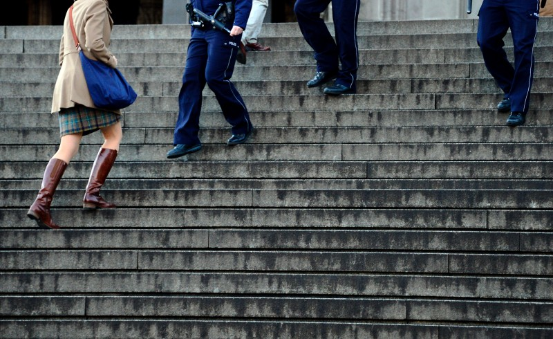 COLOGNE, GERMANY - JANUARY 09:  A woman goes past to on an policeman on the stairs between Hauptbahnhof main railway station and Cologne Cathedral on January 9, 2016 in Cologne, Germany.  (Photo by Sascha Schuermann/Getty Images)