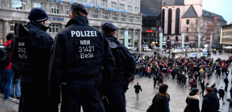 """Policemen look on as refugees from Syria demonstrate against violence near the Cologne main train station in Cologne, western Germany on January 16, 2016, where hundreds of women were groped and robbed in a throng of mostly Arab and North African men during New Year's festivities. German authorities said that nearly all the suspects in a rash of New Year's Eve violence against women in Cologne were """"of foreign origin"""", as foreigners came under attack amid surging tensions. / AFP / PATRIK STOLLARZ        (Photo credit should read )"""