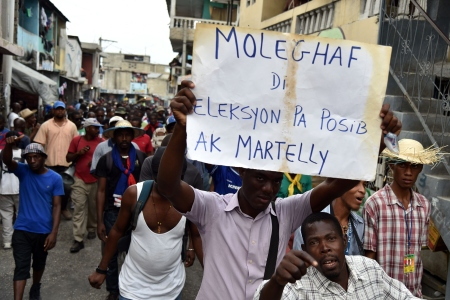 Protesters march in Port-au-Prince on January 24, 2016 to demand the resignation of Haitian President, Michel Martelly. Haiti's electoral authority postponed Sunday's planned presidential run-off amid mounting opposition street protests and voting fraud allegations. The second round of presidential elections was scheduled for January 24 between ruling party candidate Jovenel Moise and Jude Celestin but was suspended by CEP. Haiti now awaits a new calendar for the second round of presidential elections and legislatives elections. / AFP / HECTOR RETAMAL (Photo credit should read HECTOR RETAMAL/AFP/Getty Images)
