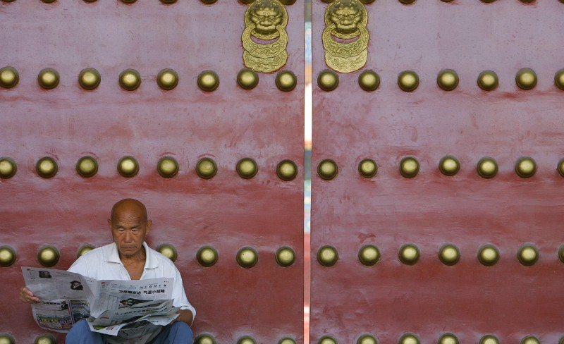 A man reads a newspaper against a closed doorway at the recently restored Imperial Ancestral Temple (Tai Miao), part of the former Imperial Palace built in 1420 during Ming Emperor Yongle's rule, and known since 1949 as the Working People's Cultural Palace, east of the Forbidden City in Beijing, 29 August 2007. China is facing mounting pressure to honour pledges of media freedom made for the 2008 Olympics as separate reports earlier this month by the Committee to Protect Journalists (CPJ) and Human Rights Watch said foreign and Chinese reporters still faced intimidation just a year before the Beijing Games open, despite China's pledges to the contrary. AFP PHOTO/Frederic J. BROWN (Photo credit should read FREDERIC J. BROWN/AFP/Getty Images)