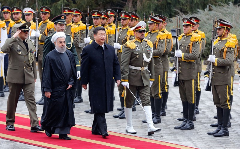 Iranian President Hassan Rouhani and Chinese President Xi Jinping (R) review troops during a welcoming ceremony on January 23, 2016 in the capital Tehran.  Chinese President Xi Jinping arrived on January 22, 2016 in Iran on the third leg of a Middle East tour aimed at boosting economic ties with the region. State news agency IRNA said Xi, accompanied by three deputy premiers and six ministers as well as a high-ranking business delegation, was greeted at Tehran airport by Iranian Foreign Minister Mohammad Javad Zarif.   / AFP / STR        (Photo credit should read STR/AFP/Getty Images)