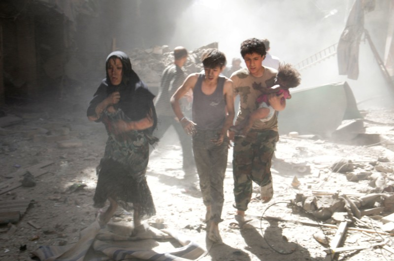 A Syrian woman and youths, one of them carrying a wounded baby, flee the site of a reported barrel-bomb attack by Syrian government forces in the northern city of Aleppo on June 26, 2014. Syria's war has killed more than 162,000 people and forced nearly half the population to flee their homes. AFP PHOTO /AMC / ZEIN AL-RIFAI        (Photo credit should read ZEIN AL-RIFAI/AFP/Getty Images)