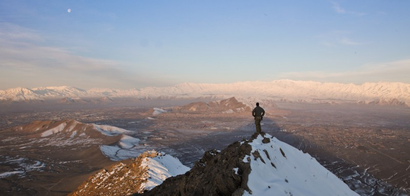 A coalition force member stands on top of a hill watching a snow-covered mountain range in Kabul province, Afghanistan, March 1, 2013. (U.S. Army photo by Sgt. Matthew Freire)
