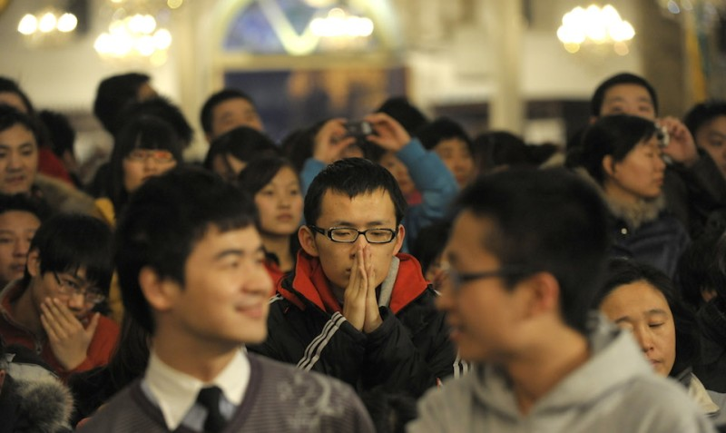 A man prays during Christmas mass at a Catholic church in Beijing on December 24, 2009. China officially allows freedom of religion, but in practice, the ruling Communist Party restricts independent worship by forcing groups to register with the government. About 15 million Protestants and five million Catholics worship at official churches, according to official data. AFP PHOTO/LIU Jin (Photo credit should read LIU JIN/AFP/Getty Images)