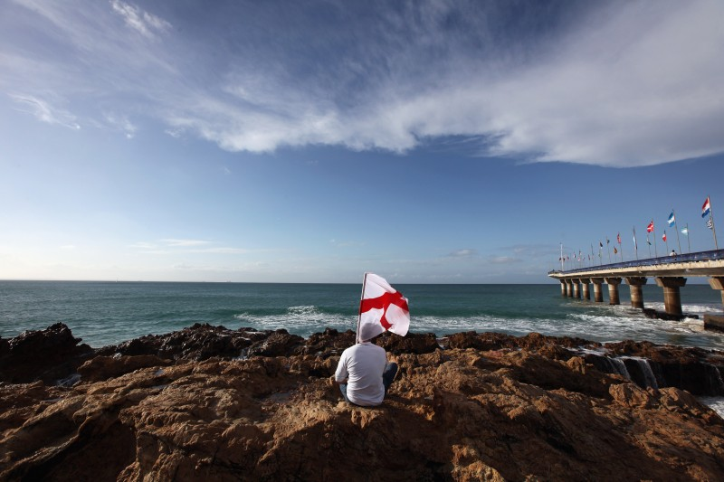 PORT ELIZABETH, SOUTH AFRICA - JUNE 22:  An England fan sits on rocks on the beach on June 22, 2010 in Port Elizabeth, South Africa. England play Slovenia at the Nelson Mandela Bay Stadium tomorrow in the third and final of their group stage matches where England need a win to continue to the next round.  (Photo by Dan Kitwood/Getty Images)