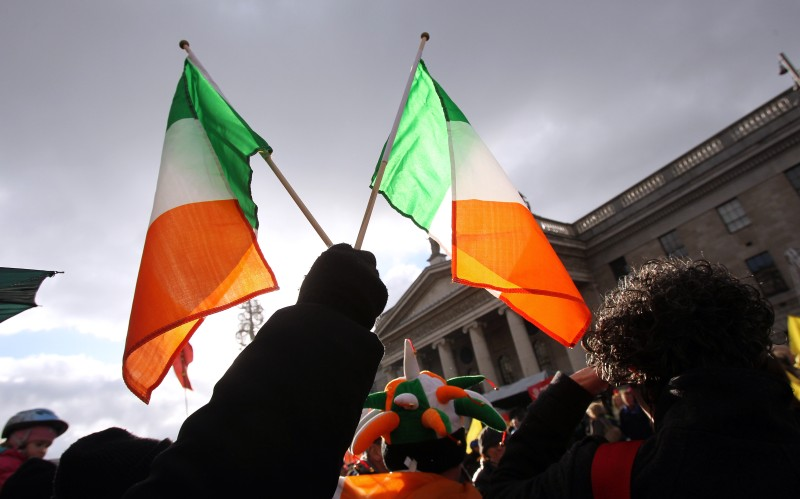 "A protester holds up two Irish flags in front of the General Post Office in Dublin on November 27, 2010 against savage cutbacks. About 50,000 Irish people took to the streets Saturday to oppose savage cutbacks needed to secure an international bailout, police said, piling pressure on the debt-laden nation's embattled government. The four-year package will cut the minimum wage and slash 25,000 public sector jobs as the one time ""Celtic Tiger"" economy tries to pay off a huge budget deficit.  AFP PHOTO / Peter Muhly (Photo credit should read PETER MUHLY/AFP/Getty Images)"
