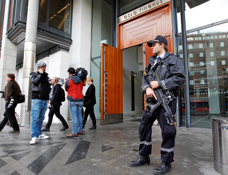 Journalists and an armed policeman stand outside the Oslo court house where the Norwegian gunman behind the twin attacks in July, Anders Behring Breivik attends his third court appearance on September 19, 2011. Prosecutors are expected to ask the court to prolong for eight weeks the detention of Anders Behring Breivik, who has confessed to the July 22 attacks that left 77 people dead. AFO PHOTO / SCANPIX NORWAY / Erik Johansen (Photo credit should read ERIK JOHANSEN/AFP/Getty Images)