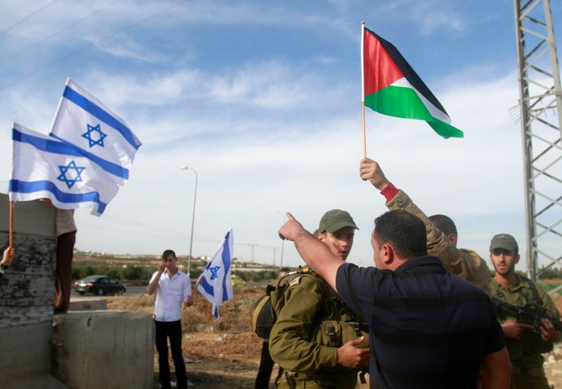 A Jewish settler (L unseen) places the Israeli flag on a road sign while Israeli troops encircle Palestinian villagers protesting after the Israeli army cut off branches of olive trees on a road leading to the Jewish settlement of Tekoa, in the occupied West Bank, southeast of the town of Bethlehem, on November 25, 2013. Israeli authorities have given the go-ahead for the construction of 829 new settler homes in the occupied West Bank, settlement watchdog Peace Now said. AFP PHOTO/MUSA AL-SHAER        (Photo credit should read MUSA AL-SHAER/AFP/Getty Images)