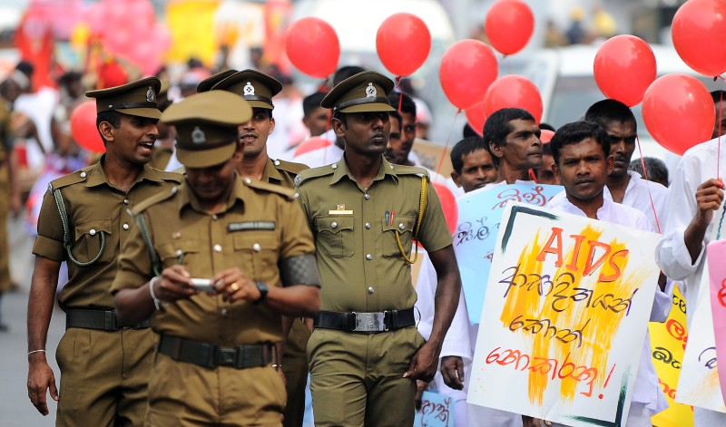 Sri Lankan prisoners hold placards as they take part in a gathering to mark World AIDS Day at a prison complex in Colombo on December 1, 2013. Some 1,808 HIV positive cases have reportedly been identified in the country between 1987 and the end of November 2013. AFP PHOTO/ Ishara S.KODIKARA        (Photo credit should read Ishara S.KODIKARA/AFP/Getty Images)