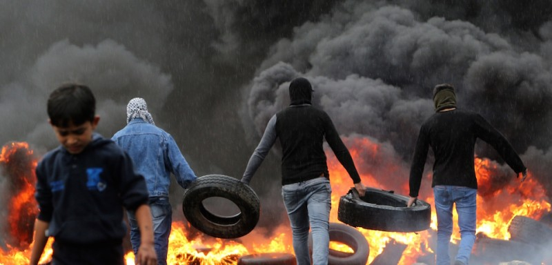 Palestinian protesters carry tire to throw on the fire during clashes with Israeli security forces (unseen) following a demonstration against the expropriation of Palestinian land by Israel in the village of Kafr Qaddum, near Nablus in the occupied West Bank, on November 21, 2014. AFP PHOTO/JAAFAR ASHTIYEH        (Photo credit should read JAAFAR ASHTIYEH/AFP/Getty Images)