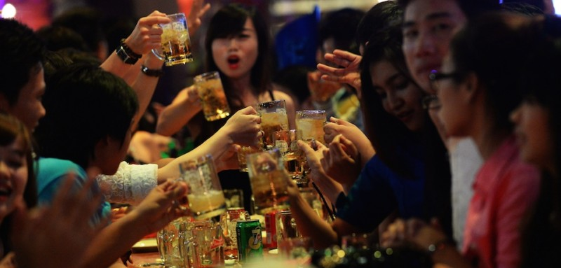 TO GO WITH STORY: Vietnam-health-social-alcohol,FEATURE by Cat Barton This picture taken on December 13, 2014 shows youngsters cheering up while drinking beer at a local open-air beer bar in downtown Ho Chi Minh City. A scantily-clad DJ gyrates to ear-splitting music as visibly drunk punters order beer towers: welcome to the Hangover, one of a new crop of beer clubs raising concerns about Vietnam's drinking culture.     AFP PHOTO / HOANG DINH NAM        (Photo credit should read HOANG DINH NAM/AFP/Getty Images)