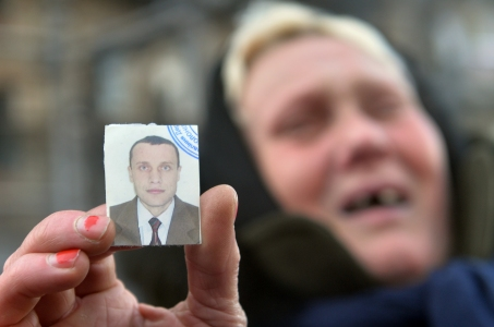 "The mother of two men, one of them, as she claims, was killed and the other one is missing, holds a picture of her lost son as she cries during a rally of mothers of the protesters in front of a policemen line facing anti-government opposition activists in the center of Kiev on January 31, 2014. Ukraine's military on Friday called on President Viktor Yanukovych to take ""urgent steps"" to ease turmoil in the country, weighing in for the first time on the ex-Soviet nation's worst crisis since independence. Ukrainian President Viktor Yanukovych on Friday signed a law offering an amnesty to jailed opposition activists and repealed controversial laws cracking down on protests, his office said. AFP PHOTO/ SERGEI SUPINSKY (Photo credit should read SERGEI SUPINSKY/AFP/Getty Images)"