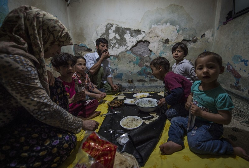 ANKARA, TURKEY - JULY 11: A Syrian refugee family living in an abandoned house, eats Iftar meals distributed by local municipalities and nongovernmental organizations during the Islam's holy fasting month of Ramadan on July 11, 2015 in Ankara, Turkey. (Photo by Mustafa Kamaci/Anadolu Agency/Getty Images)