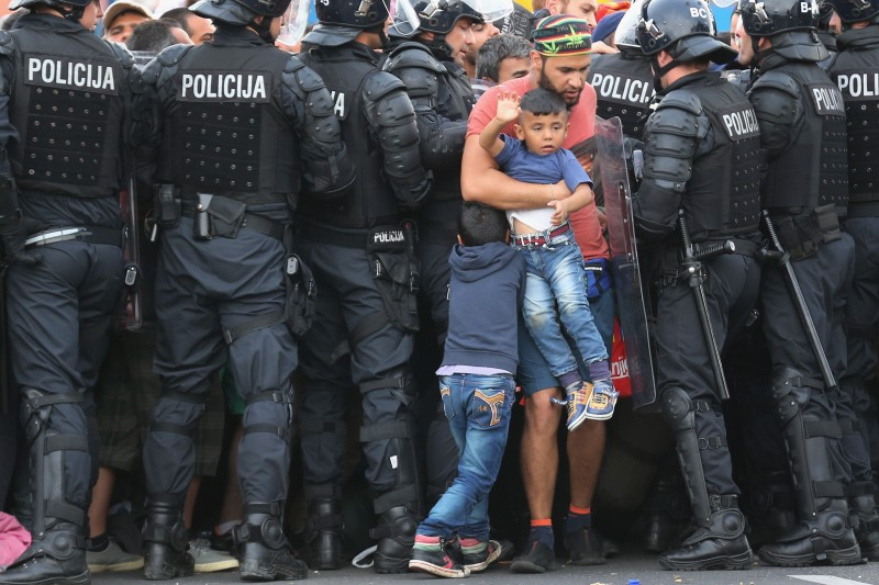 HARMICA, CROATIA - SEPTEMBER 19:  A man and his children are allowed through as migrants are held back by Slovenian riot police in the small Croatian village of Harmica on September 19, 2015 in Harmica, Croatia. Last night police had to use pepper spray to hold back migrants at the small border crossing, today they are allowing small groups to cross and are being bussed to a registration centre in Slovenia. Thousands of migrants are trying back roads and tracks through villages to gain access to Slovenia and the EU since Hungary fenced off its border with Serbia earlier this week.  (Photo by Christopher Furlong/Getty Images)