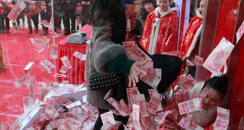 HANGZHOU, CHINA - JANUARY 26: (CHINA OUT) Tourists grab 100-yuan banknotes over a blower in the glass house at Song Dynasty Town on January 26, 2016 in Hangzhou, Zhejiang Province of China. Song Dynasty Town gave away 5 million yuan (about 760,000 USD) as a feedback to the tourists to celebrate the Spring Festival. 10 tourists were selected to catch money over a blower in the glass house, and one of them caught 18,300 yuan (about 2,781.6 USD) as the most lucky one.  (Photo by ChinaFotoPress/Getty Images)