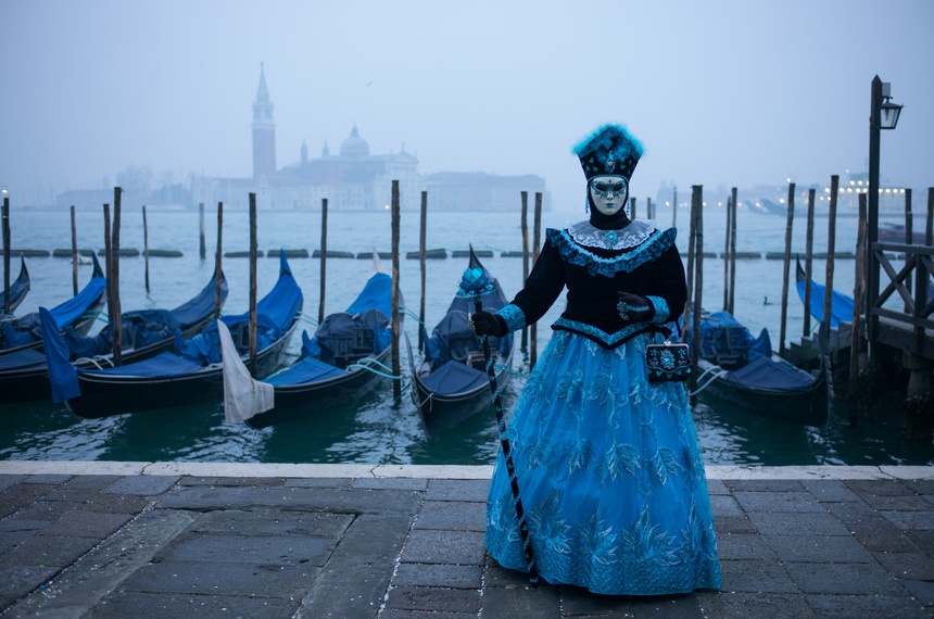 VENICE, ITALY - JANUARY 30:  A woman dressed in a carnival costume poses early morning for pictures in front of gondolas on January 30, 2016 in Venice, Italy. The 2016 Carnival of Venice will run from January 23 to February 9 and includes a program of gala dinners, parades, dances, masked balls and music events.  (Photo by Marco Secchi/Getty Images)