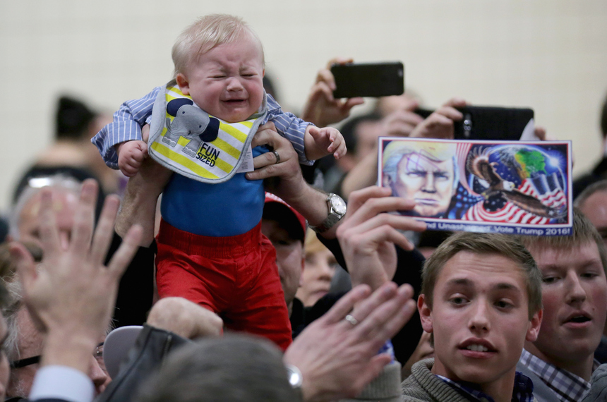 COUNCIL BLUFFS, IA - JANUARY 31:  A Trump supporter holds his child aloft for Republican presidential candidate Donald Trump to see, as other supporters clamour for autographs at a campaign rally at the Gerald W. Kirn Middle School on January 31, 2016 in Council Bluffs, Iowa. Trump and other presidential hopefuls are in Iowa trying to gain support and crucial votes for tomorrow's caucuses.  (Photo by Christopher Furlong/Getty Images)