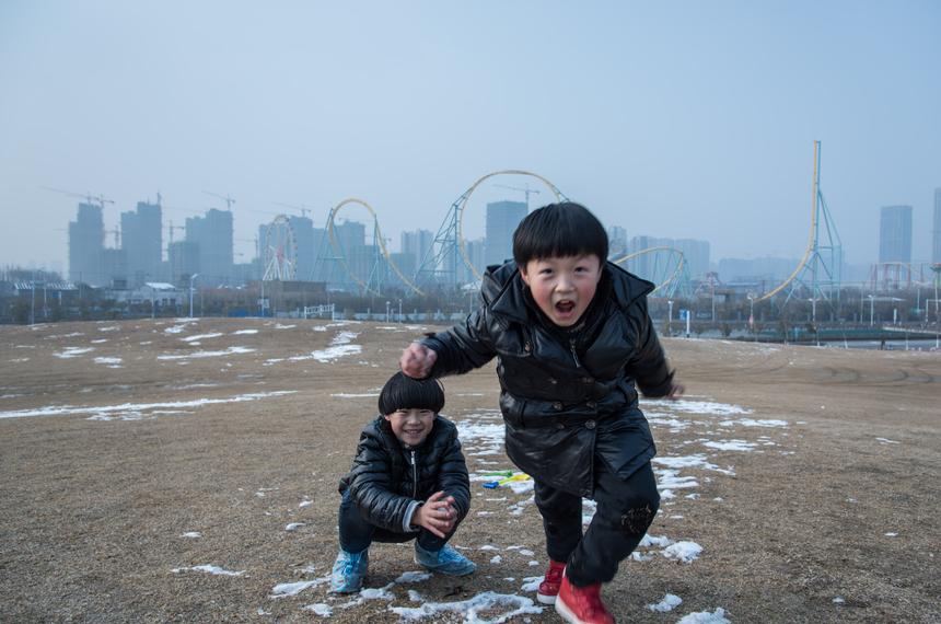 HEFEI, CHINA - FEBRUARY 01:  Twins play in front of a new-built residential area on February 1, 2016 in Hefei, China.  (Photo by Xiao Lu Chu/Getty Images)