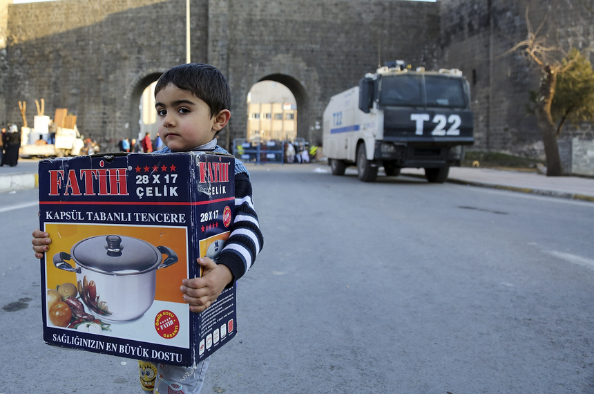 DIYARBAKIR, TURKEY - FEBRUARY 01:  A boy walks carrying a pot during a short break in the curfew on February 1, 2016 in Diyarbakir, Turkey. Parts of Diyarbakir, that is considered the capital of Turkey's Kurdish regions, have been under a Turkish army imposed curfew for more than two months.  (Photo by Awakening/Getty Images)