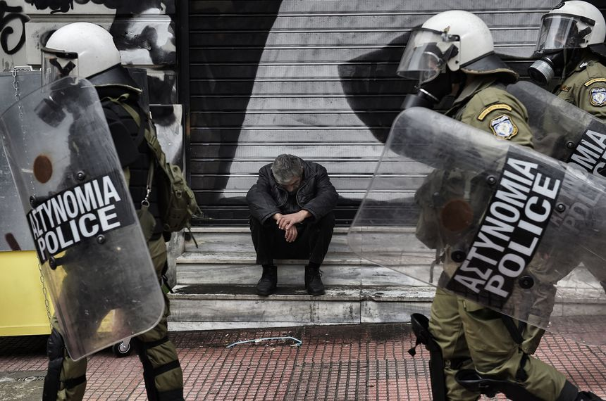 TOPSHOT - A man sits outside a closed store as demonstrators clash with riot police in Athens, on February 4, 2016.  Thousands of people marched across Greece on February 4, 2016 as diverse classes united in a crippling general strike over a pension overhaul that has sparked a major backlash against embattled leftist Prime Minister Alexis Tsipras / AFP / ARIS MESSINIS        (Photo credit should read ARIS MESSINIS/AFP/Getty Images)