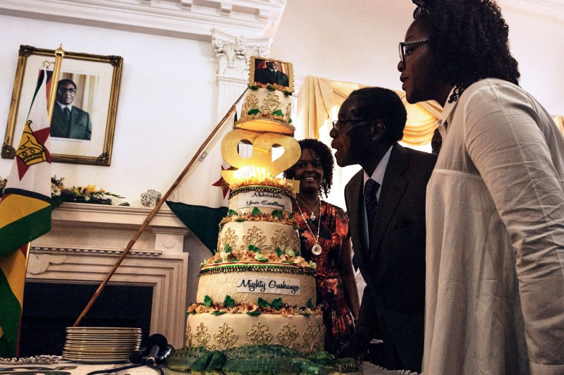 Zimbabwe President Robert Mugabe (C), flanked by his wife Grace Mugabe (L) and daughter Bona (R), blows candles on his cake during a suprise party  hosted by the office of the President and Cabinet at State House in Harare, on February 22, 2016 to celebrate his 92nd birthday.  Zimbabwean President becomes the worlds oldest leader with no plans to step down as feuding over his successors threatens to tear his ruling ZANU-PF apart. / AFP / JEKESAI NJIKIZANA        (Photo credit should read JEKESAI NJIKIZANA/AFP/Getty Images)