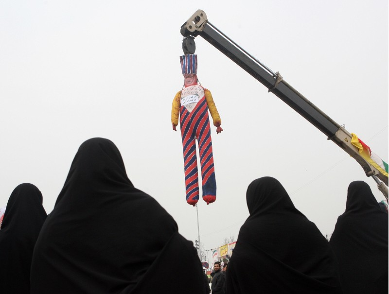 """Veiled Iranian women look at an effigy of an executed 'Uncle Sam' with anti-US and anti-Israel slogans written on it during a rally held in Tehran to mark the 29th anniversary of the Islamic revolution on February 11, 2008. Hundreds of thousands of Iranians shouted """"Death to America"""" and pledged their loyalty to the Islamic republic as they celebrated the revolution's anniversary while President Mahmoud Ahmadinejad said in a speech on the occasion that the West was only """"playing with pieces of paper"""" in its pressure over Iran's nuclear programme and launched a bitter tirade against his domestic opponents. AFP PHOTO/BEHROUZ MEHRI (Photo credit should read BEHROUZ MEHRI/AFP/Getty Images)"""