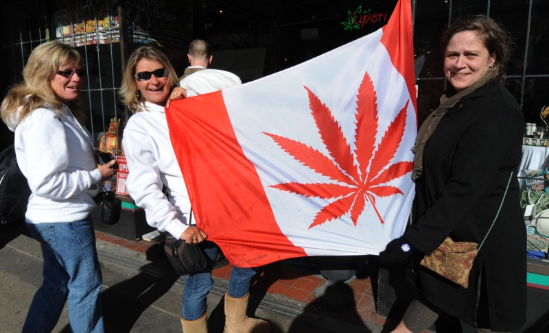 Visitors pose in front of a flag similiar to the Canadian one but showing a cannabis plant instead of a maple leaf at a store in Eastside Vancouver during the Vancouver Winter Olympics on February 22, 2010.         AFP PHOTO/Mark RALSTON      (Photo credit should read MARK RALSTON/AFP/Getty Images)