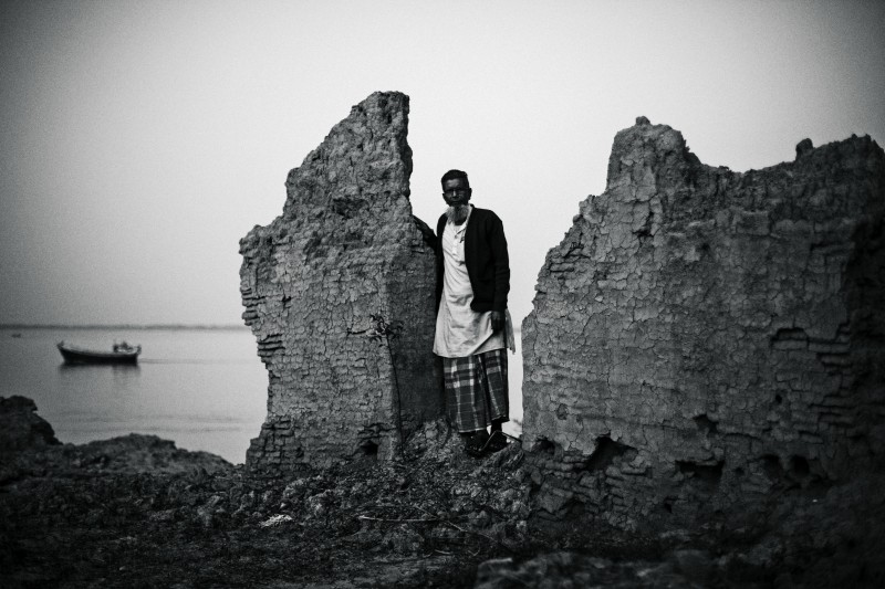 "A portrait of Sk. Aptauddin and he's destroyed house by sea water.   Photograph from the series "" The story of a dead horse"".  Photo of Jordi Pizarro ©   **Do not use this photograph with permission by photographer Jordi Pizarro. © all rights reserved. 2015  STORY:   Ghoramara is the name of a Island, in bengalí language Ghoramara minds ""a dead horse"" long time ago there were Bengali tigers in the island. They say that one of them killed the horse of a British settler and that it is the discovery of the animal's dead body what gave the place its name.  In only four decades Ghoramara has lost more than 75 percent of its territory. Erosion and sea rising due to climate change are responsible for such a loss. While expert look for scientific explanations, the island's five thousand inhabitants strive to protect what is left and get prepared for the worst.  It is a race against time with little tools and expertise, done more with the heart than with preparedness in an effort to save their way of life in one of the world's ecosystems most vulnerable to climate change. A struggle that won't be probably mentioned in next December UN climate change summit, although recent reports warn that the island is likely to disappear within the next six  to eight years."