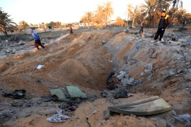 Libyans stand next to a crater and debris at the site of a jihadist training camp, targeted in a US air strike, near the Libyan city of Sabratha on February 19, 2016.  A US air strike on a jihadist training camp in Libya killed dozens of people Friday, probably including a senior Islamic State group operative behind attacks in Tunisia, officials said. / AFP / MAHMUD TURKIA        (Photo credit should read MAHMUD TURKIA/AFP/Getty Images)