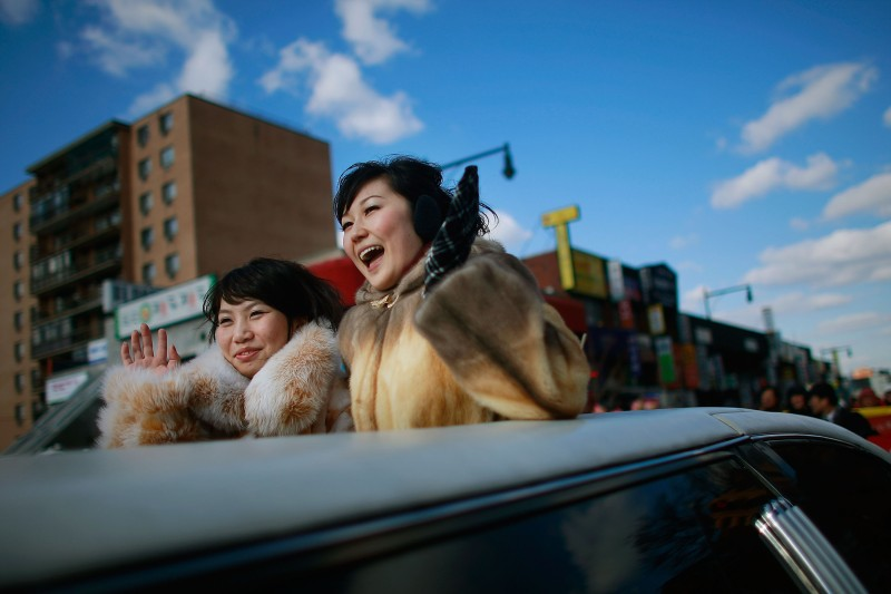 NEW YORK - JANUARY 31:  Women wave while riding in the Flushing Chinese New Year Parade January 31, 2009 in the Queens borough of New York City. Chinese New Year marks the start of the new year on the lunar calendar with 2009 being the year of the Ox.  (Photo by Mario Tama/Getty Images)