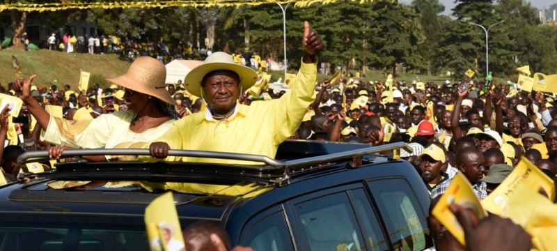 Uganda's President Yoweri Museveni (C) and his wife Janet Museveni wave from to supporters  from atop their car as they arrive for a rally of the ruling National Resistance Movement (NRM) party at Kololo Airstrip in Kampala on February 16, 2016.  Uganda's presidential contenders held their final campaign rallies on February 16, a day after opposition supporters clashed with police leaving at least one person dead. Museveni and his ruling National Resistance Movement (NRM) party is widely predicted to win a fifth term in power in polls, and warned at a rally against voting for his rivals. / AFP / Isaac Kasamani        (Photo credit should read ISAAC KASAMANI/AFP/Getty Images)