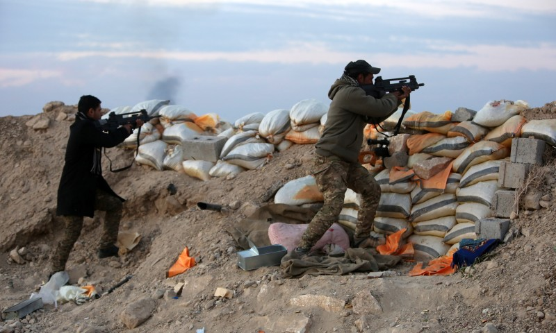 Iraqi pro-government forces fire their weapons during clashes with Islamic State (IS) group fighters, on the eastern outskirts of Ramadi, the capital of Anbar province on January 31, 2016. / AFP / AHMAD AL-RUBAYE        (Photo credit should read AHMAD AL-RUBAYE/AFP/Getty Images)