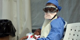 A Liberian health worker holds a baby infected with the Ebola virus on October 18, 2014 at the NGO Medecins Sans Frontieres (Doctors Without Borders) Ebola treatment center in Monrovia. The death toll in the world's worst-ever Ebola outbreak has shot past 4,500, killing at least half of the more than 9,000 people infected, fresh World Health Organization figures showed on October 17. AFP PHOTO / ZOOM DOSSO        (Photo credit should read ZOOM DOSSO/AFP/Getty Images)