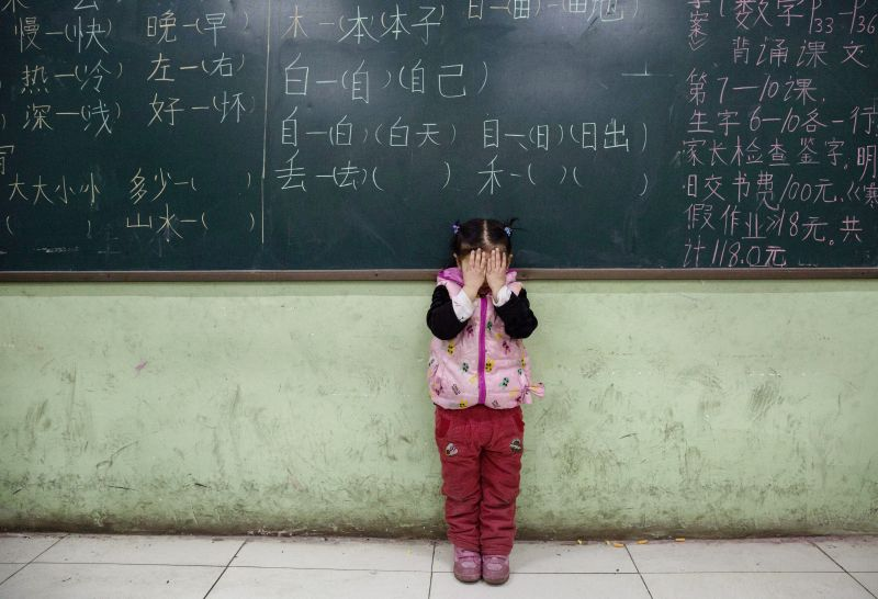 BEIJING, CHINA - DECEMBER 18: A Chinese student who is a child of migrants does eye exercises as part of a class at an un-official school on December 18, 2015 in Beijing, China. Schools for children of migrants are often unofficial or unrecognized by the state, and were established as a response to the education void created by the decades-long household registration or hukou system. A person's hukou entitles them to social services in their birthplace, meaning millions of Chinese who have migrated from rural areas to cities have been denied rights to urban public services. Reforms to the hukou system come after heavy criticism that it has aggravated a deep social divide in China. The changes could pave the way for up to 70 million children of migrant workers left behind in villages to join their parents in cities.  (Photo by Kevin Frayer/Getty Images)