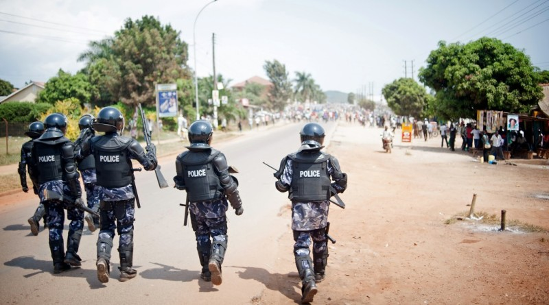Riot police advance towards a crowd of opposition supporters in the centre of Ggaba, a suburb of Kampala, on February 18, 2016, during Uganda's national elections. Voters refused to use a polling station at Ggaba after an unsealed ballot box was found among voting materials, and police moved in to disperse the crowds as they began to protest. Voting in Uganda's national elections was due to begin at 07:00 am (0400 GMT) but was stalled for several hours in some polling stations in parts of the city and the surrounding Wakiso district, where ballot boxes and papers did not arrive on time. / AFP / Will Boase        (Photo credit should read WILL BOASE/AFP/Getty Images)