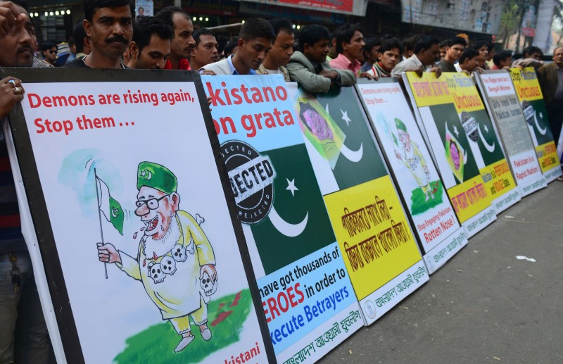 Bangladesh Awami League supporters protest with anti-Pakistan placards in Dhaka on December 23, 2013. The activists demonstrated against Pakistan's reaction over the execution of Abdul Quader Molla, a top Islamist leader convicted of war crimes. AFP PHOTO/Munir uz ZAMAN        (Photo credit should read MUNIR UZ ZAMAN/AFP/Getty Images)