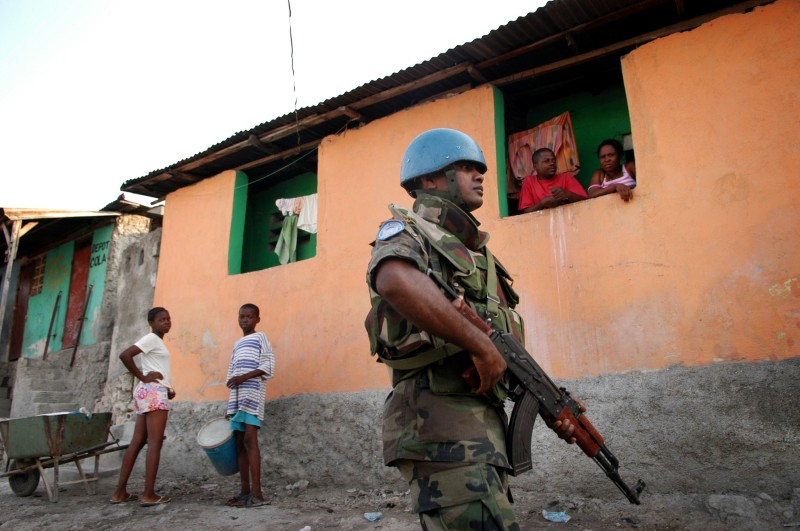 """PORT-AU-PRINCE, HAITI - MARCH 21:  United Nations (UN) soldiers from Sri Lanka patrol the slum """"City of God"""" March 21, 2005 in the downtown area of Port-au-Prince, Haiti. At least two members of the Haitian former military and two UN soldiers died in a gun battle March 20, marking the first lost of life to the UN peace force since it arrived in Haiti.  (Photo by Shaul Schwarz/Getty Images)"""